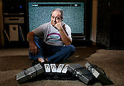 Lou Therson of Richland poses for a portrait with his old DirecTV receivers and remotes. Fed up with the feud between DirecTV and Fox and the resulting customer service headaches he encountered trying to get the Seahawks' playoff game against the Bears prompted him to switch to DISH Network, which he says he's been very happy with.