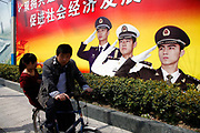 A man rides his bike past a large poster showing saluting Chinese People's Liberation Army (PLA) soldiers in Shanghai, China, on 01 April 2011.  In its recently released national defense white paper, China has tried to praise its military modernization while assuring foreign countries, especially the United States, that its build ups are not geared toward expansionism and regional dominance.