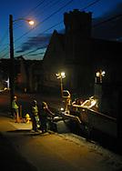 Workers from Kirila Contractors begin repaving East State Street in Sharon, Pennsylvania at sundown.