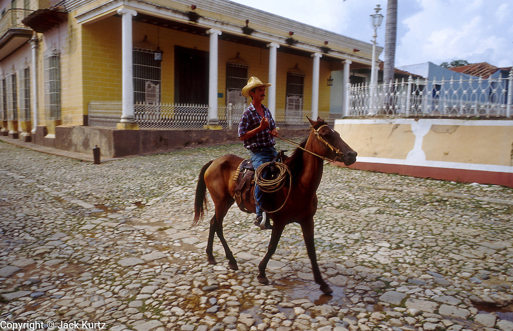 23 JULY 2002 - TRINIDAD, SANCTI SPIRITUS, CUBA: A man rides his horse through Plaza Mayor, the main square in the colonial city of Trinidad, province of Sancti Spiritus, Cuba, July 23, 2002. Trinidad is one of the oldest cities in Cuba and was founded in 1514. .PHOTO BY JACK KURTZ
