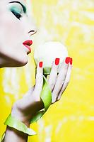 beautiful caucasian woman portrait holding an apple studio on yellow background