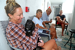 Christie Sadowski and her dog Gio, along with neighbors Ann and Jim Pinkerton, are relieved that Hurricane Irma did not hit their Hollywood neighborhood as bad as expected. They are all neighbors at the Sheridan by the Beach condominium. Photo by Susan Stocker/Sun Sentinel/TNS/ABACAPRESS.COM