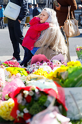 © Licensed to London News Pictures. 25/03/2017. London, UK. A mother and daughter their respects to the victims of Westminster terror attack in Parliament Square, London on 25 March 2017. Photo credit: Tolga Akmen/LNP