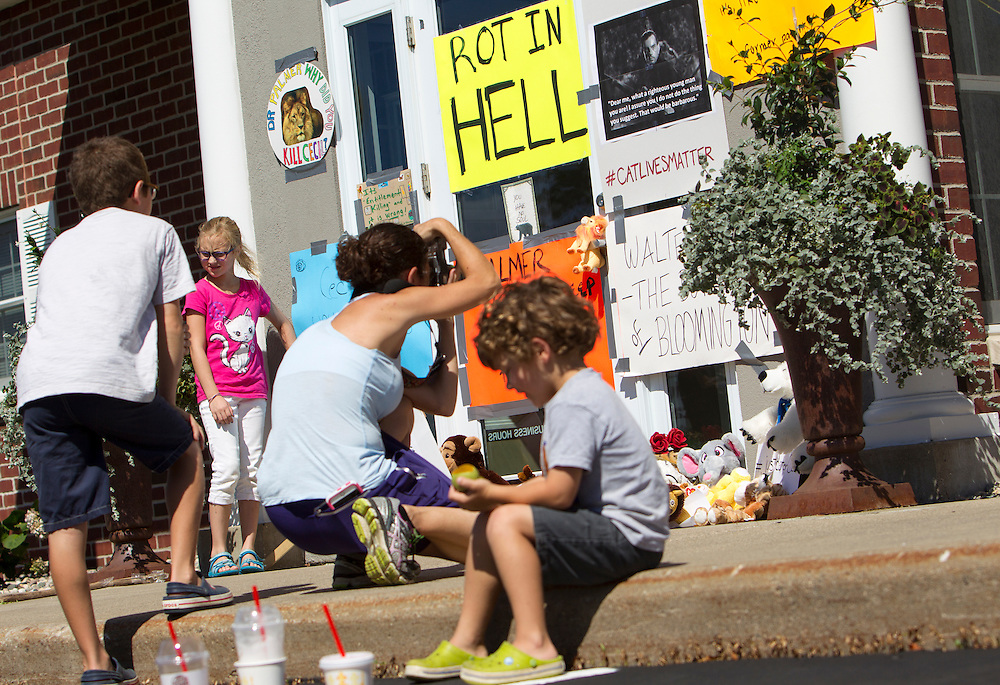 Photographer and local resident Rebecca Waldock documented signs on the door at a protest at the dental office of lion hunter Walter James Palmer in Bloomington, MN, July 29, 2015. She brought her children Jack, 9, left, and Sam, 5, seated, because she thinks it is important for them to see peaceful expression of protest.  The behavior of the crowd gathered was peaceful.
