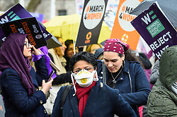 © Licensed to London News Pictures. 08/03/2020. LONDON, UK. A woman wearing a facemask takes part in the annual March 4 Women on International Women's Day. The event this year celebrates the power and passion of women and girls who are on the frontline of responding to climate change.  The walk through central London from Whitehall Place ends with a rally in Parliament Square.  Photo credit: Stephen Chung/LNP