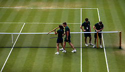 Ground staff adjust the net on court eighteen on day seven of the Wimbledon Championships at the All England Lawn Tennis and Croquet Club, Wimbledon.