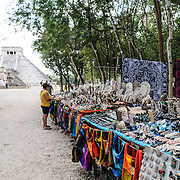 Market stalls selling local souvenirs and handicrafts to tourists visiting Chichen Itza Mayan ruins archeological site in Mexico. El Castilla is in the background.