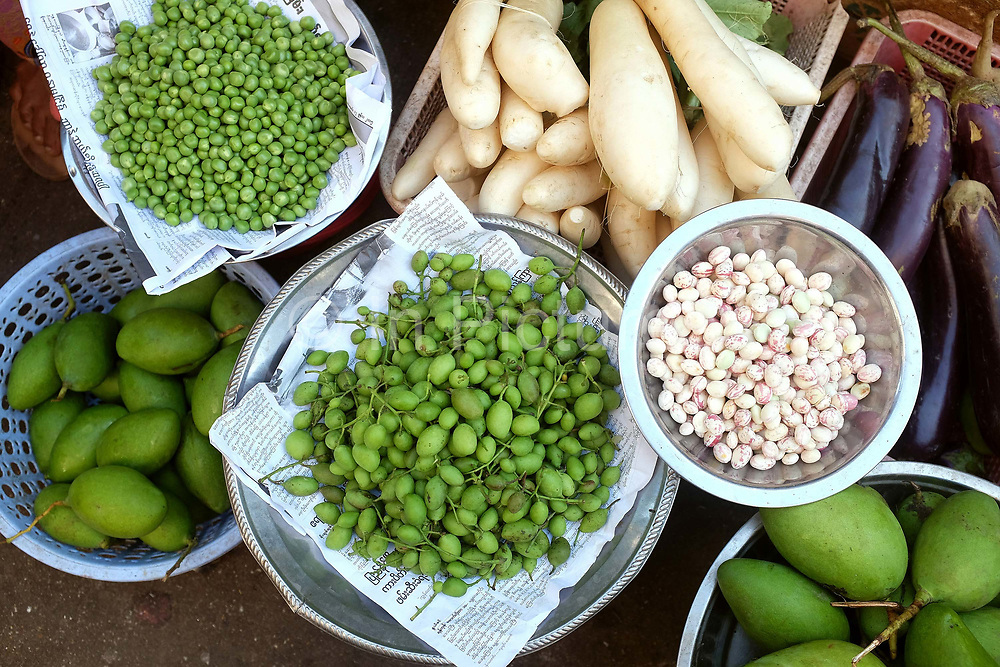 Fresh fruit and vegetables for sale at an early morning street market on 16th January 2016 in Yangon, Myanmar.  A large variety of local products are available for sale in fresh markets all over Yangon, all being sold on small individual stalls