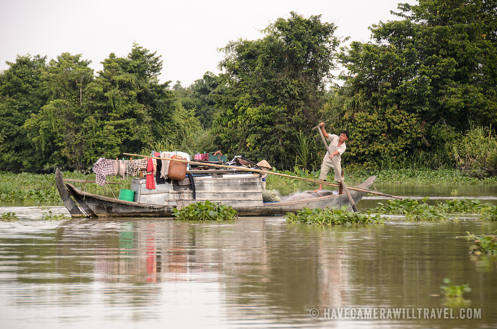 A small fishing boat goes amongst the reeds on the Saigon River in Ho Chi Minh City, Vietnam.