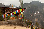 Prayer wheel and prayer flags at a hut on the trail up to the Taktsang Monastery with the monastery in the distance