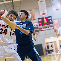 Gallup Bengal Johnny Blueeyes (34) tires to hold onto possession ahead of Window Rock Scout Kalem Roanhorse (33) during the Bengal Boys Basketball Invitational Tournament third-place game at Gallup High School Saturday.