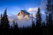 Heavy Runner Mountain rises out of the clouds in Glacier National Park, Montana.