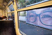 Looked upon by the large eyes from a Specsavers opticians ad, a train passenger leans against the carriage window of a train stopped at Denmark Hill in south London, on 31st October 2020, in London, England.