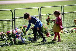 © Licensed to London News Pictures. 17/04/2021. Windsor, UK. Children place flowers on The Long Walk near Windsor Castle, in Windsor, Berkshire, ahead of the funeral of Prince Philip, The Duke of Edinburgh. Prince Philip, the Consort of the longest reigning English monarch in history, Queen Elizabeth II, died on 9 April 2021, two months before his 100th birthday. . Photo credit: Ben Cawthra/LNP