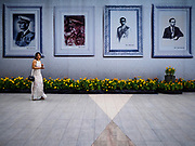 18 FEBRUARY 2017 - BANGKOK, THAILAND: A woman walks past portraits of Bhumibol Adulyadej, the Late King of Thailand, hanging in front of Paragon shopping mall in Bangkok. The revered monarch died on Oct. 13, 2016 and will be cremated on Oct 25, 2017. Thailand's mourning period ends on October 29, 2017.     PHOTO BY JACK KURTZ