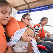 CAPTION: Kalebe is fast asleep in Jeane's arms. Beside them is Karen, a medical student who's accompanying the Smile Train team, and Nelson, who is providing translation support. Kalebe has an incomplete bilateral cleft of the lip and the alveolus. The doctors feel that since his palate and teeth are relatively normal, it is possible to correct his condition with just one operation. LOCATION: Rio Marañón, near Tabatinga, Amazonas, Brazil. INDIVIDUAL(S) PHOTOGRAPHED: Adults, from left to right: Jeane Gomes, Karen Costa and Nelson Campos; child: Kalebe Rabelo.