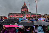 """San Francisco City Hall's pink lights surprise the crowd, turning on just as the crowd begins to march from the rally at Civic Center Plaza. Above the crowd, a sign reads, """"I've seen better cabinets at IKEA."""""""