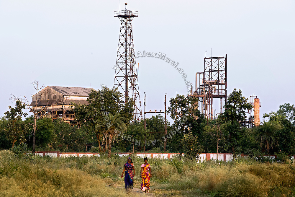 Two women are walking past the abandoned Union Carbide (now DOW Chemical) industrial complex, in Bhopal, Madhya Pradesh, central India.