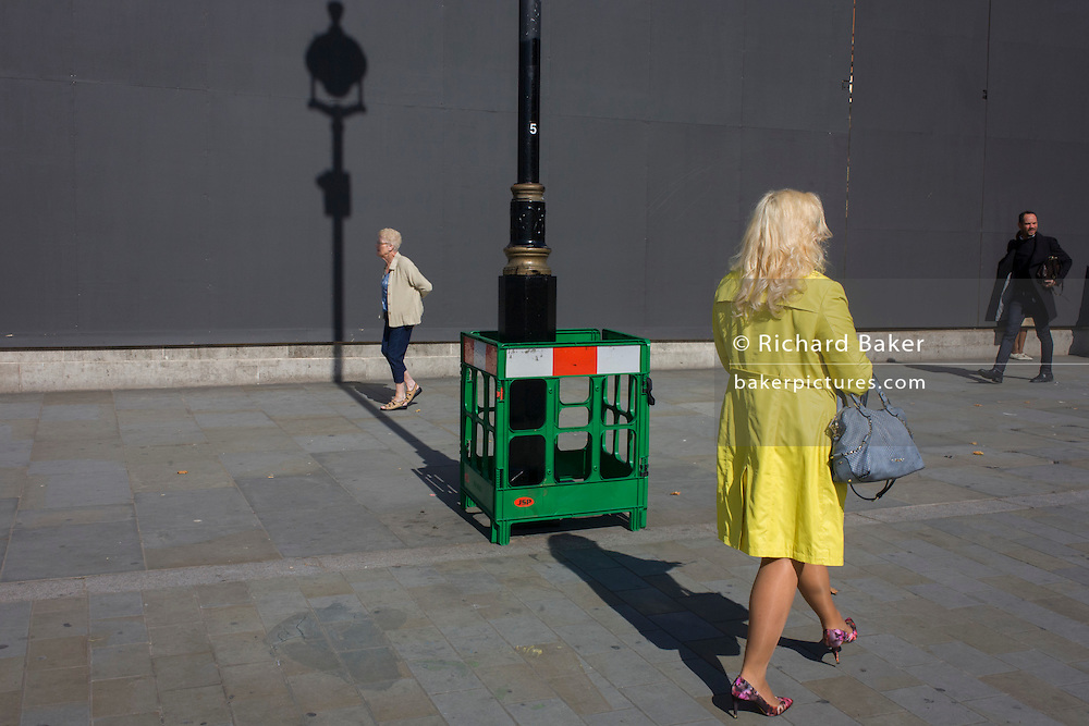 Women with a lamp post shadow against a grey construction hoarding in central London's Trafalgar Square.