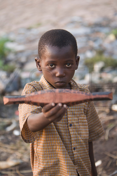 """A boy shows a miniature """"pinasse"""", the tipical canoe from the regions. At the confluence of the Niger and the Bani rivers, between Timbuktu and Ségou, Mopti is the second largest city in Mali, and the hub for commerce and tourism in this west-african landlocked country."""