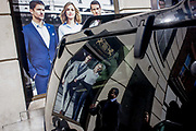 Models on a poster of a stylish clothing shop for business people are reflected in the rear of a black vehicle parked in the City of London. Alongside very good-looking and stylish men wearing sharp suits - the latest in 2015 city fashion - we see the styles of contemporary London in the City of London, the capital's financial heart and business people are walking along this side street off Cannon Street.