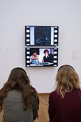 Visitors watching video installation Das Kapital/ Capital by Joseph Beuys , Babeth Mondini-VanLoo at Hamburger Bahnhof modern art museum in Berlin, Germany