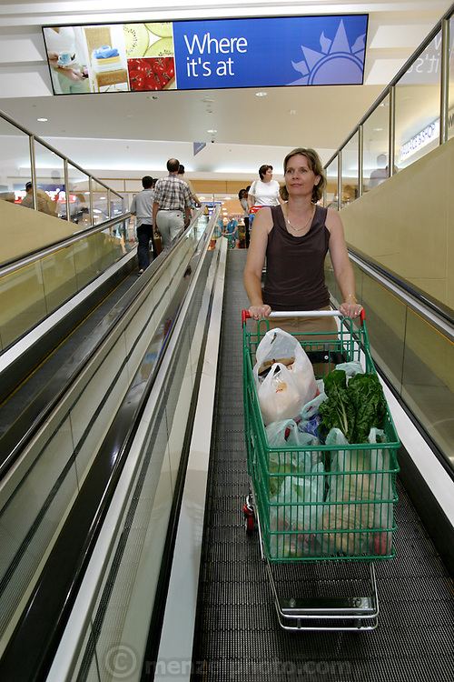 (MODEL RELEASED IMAGE). Natalie Molloy rides down the shopping-cart-friendly escalator to her car in the shaded parking garage after she has finished buying a week's worth of groceries at a Woolworth's supermarket. (Supporting image from the project Hungry Planet: What the World Eats.)