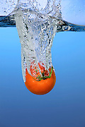 A tomato is dropped in water, creating a splash.