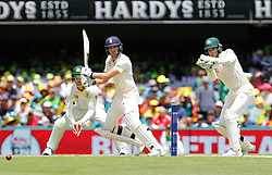 England's Dawid Malan plays a shot as Tim Paine looks on during day two of the Ashes Test match at The Gabba, Brisbane.