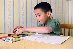 Young boy sitting at table choosing crayons to colour in picture,