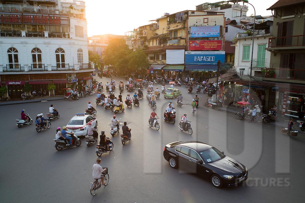 Traffic chaotically circulates around the roundabout north of Hoan Kiem Lake, Hanoi, Vietnam, Southeast Asia