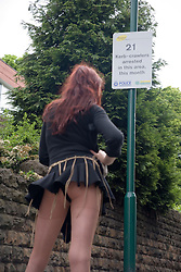 Working prostitute reading a Nottingham City Police sign warning Kerbcrawlers of 21 arrests in the area,