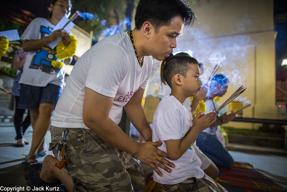 27 JANUARY 2013 - BANGKOK, THAILAND:   A man teaches his son the ritual of prayer for Thaipusam at Dhevasathan (the Brahmin Shrines) on Dinso Rd in Bangkok. Thaipusam is a Hindu festival celebrated primarily by the Tamil community in South East Asia on the full moon in the Tamil month of Thai (Jan/Feb). Pusam refers to a star that is at its highest point during the festival. The festival commemorates both the birthday of the Hindu god Murugan, son of Shiva and Parvati, and the occasion when Parvati gave Murugan a vel (a lance) so he could vanquish the evil demon Soorapadman. The holy day is celebrated by Brahmins in Thailand. Brahmanism was the court religion before Buddhism came to Thailand and before the foundation of Sukhothai. Both religions are combined in the Thai way of life and its customs and ceremonies.     PHOTO BY JACK KURTZ