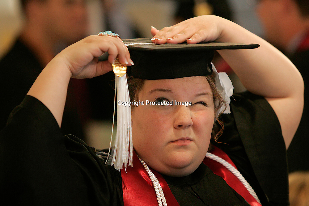 TRIBUNE PHOTO/SANTIAGO FLORES<br /> Desiree Back of Walkerton looks up as she fixes her tassle prior to the start of the Holy Cross College commencement on Saturday afternoon.