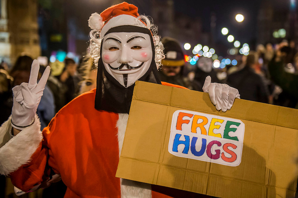 """Santa gives out free hugs - The Million Mask March - anti-establishment protesters in V for Vendetta-inspiredGuy Fawkes masks march from Trafalgar Square to Parliament Square. It was organised by Anonymous, the anarchic 'hacktivist' network. The movement is also closely identified with the Occupy protests, Wikileaks, and the Arab Spring. The UK Anonymouswebsitedescribes the march on Parliament as a """"protest against austerity … the infringement of our rights … mass surveillance … war crimes … corrupt politicians."""""""