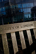 City of London bench and modern city background. With sunlight illumination the wooden slats and cross-bar, we see the modern city in the background and the carved lettering of the Corporation of London's on the bench, used by passers-by at lunchtimes. The City of London is the capital's historic centre and financial heart, first occupied by the Romans in AD43 then expanded during following centuries until today. The Square Mile, as the City is also known, has a resident population of under 10,000 but a daily working population of 311,000.