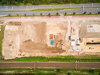 Aerial view above of construction site near empty road, Netherlands.