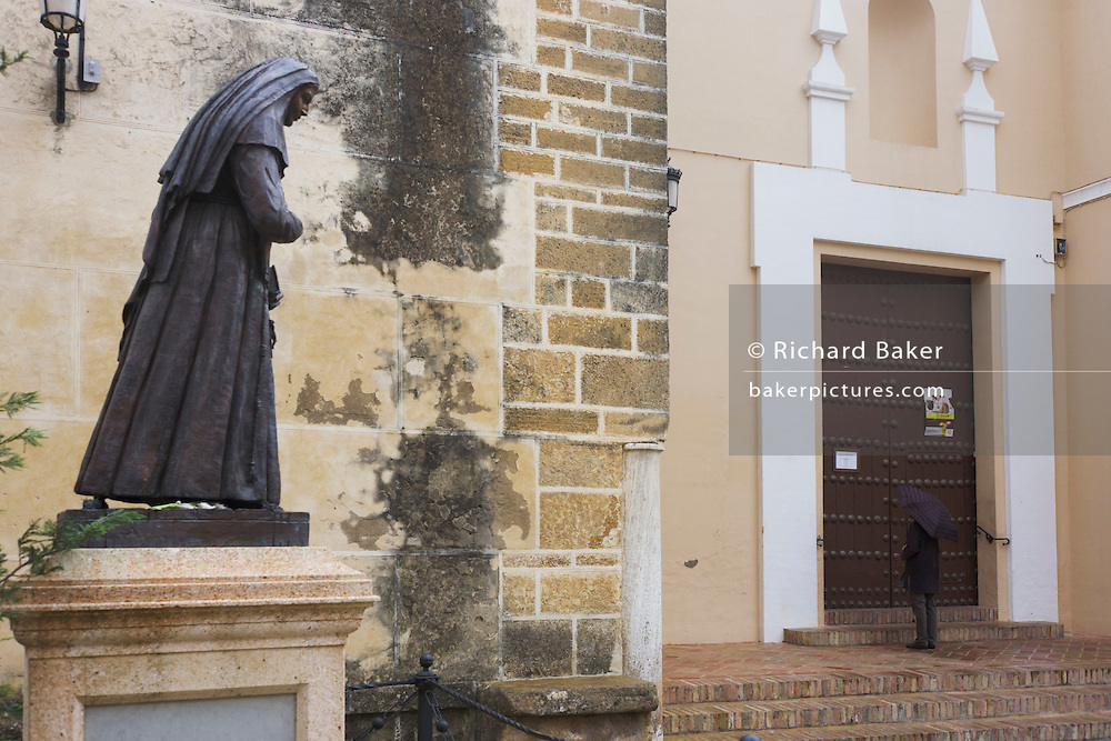 A lone Catholic stands awaiting the opening of doors at the Church of Santiago in Carmona, Andalucia.