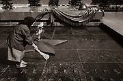 An elderly woman stoops to sweep the Tomb of the Unknown Soldier just off Red Square in Moscow, Russia. 1990