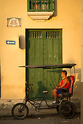Bicycle taxi and his driver on city street, Havana, Cuba