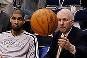 Spurs head coach Gregg Popovich, right, reaches out to catch a basketball as Spurs forward Tim Duncan, left, sits on the bench during an NBA basketball game against the Jazz in Salt Lake City, Wednesday Jan. 26, 2011. (AP Photo/Colin E Braley)