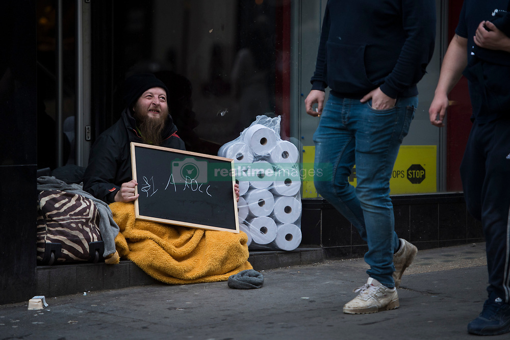 March 17, 2020, London, United Kingdom: A man sits in a doorway in London's West End, holding a sign offering to sell loo roll for one Pound each to passers buy amid a worldwide pandemic due to the Coronavirus. The growing numbers of cases in the UK have caused people to panic buy resulting in shops running out of loo-roll. (Credit Image: © Ben Stevens/i-Images via ZUMA Press)