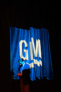 A man stands in the projected image of a GM logo while Dan Akerson, chief executive officer of General Motors Co. ( GM), makes his presentation in Shanghai, China, on Wednesday, Sept. 21, 2011. China's auto market will grow by 13 million units in 10 years, Akerson said at a briefing.