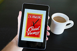 Man reading The Casual Vacancy by JK Rowling  e-book on   Google Nexus tablet computer running android operating system