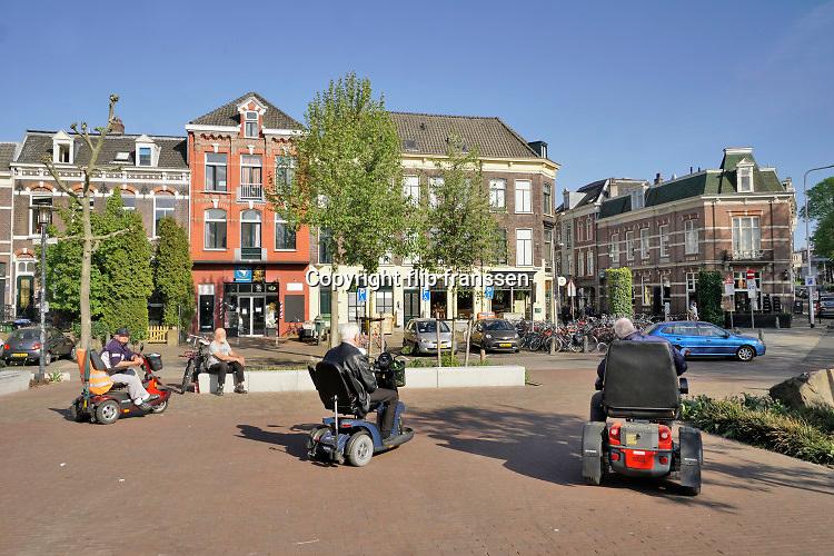 Nederland, Nijmegen, 30-4-2020  Een viertal ouderen met beperking zijn bij elkaar op een pleintje in de stad . Ze houden goed de voorgeschreven afstan tot elkaar .Foto: Flip Franssen