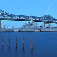 Last week my travel New England Photography lead me to Fall River, MA. Battleship Cove was on my photo bucket list for quite some time and I am glad I finally was able to get down there for sunrise. Sunset is also a good time photographing these World War II naval vessels below the Braga Bridge. Upon arrival I explored my options while looking for a decent foreground element that I could incorporate into my composition. Not long into my quest I came across these mooring poles perfectly lined up beautifully. Equipped with a Gitzo tripod, a Canon Mark IV and 28-70mm zoom lens I got to work in the freezing morning hours. I like working with this lens as it provides a lot of freedom when composing a shot. Set at 50mm, I selected an f/14 aperture  with an ISO100 setting. The resulting long-exposure time was 25 section which provided a smooth waterscape while boats, bridge and the wooden poles remained in sharp focus. <br /> <br /> During post-processing I adjusted brightness, contrast, vibrancy and color saturation before removing dust spots and sharpening the final image of Battleship Cove.<br /> <br /> Good light and happy photo making!<br /> <br /> Juergen<br /> Licensing: http://www.rothgalleries.com<br /> Photo Prints: https://juergen-roth.pixels.com/<br /> Photo Blog: http://whereintheworldisjuergen.blogspot.com<br /> Instagram: https://www.instagram.com/rothgalleries<br /> Twitter: https://twitter.com/naturefineart<br /> Facebook: https://www.facebook.com/naturefineart