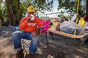 18 AUGUST 2020 - CEDAR RAPIDS, IOWA: Cedar Rapids was the state's hardest hit city by tALSANDY PHILLIP, originally from Micronesia, drinks his morning coffee at the outdoor kitchen residents made at Cedar Terrace Apartments in Cedar Rapids. The complex was destroyed by the derecho wind storm. Most of the tenants in the complex are refugees from Africa and Micronesia who have chosen the camp in front of the buildings rather than move to shelters because they're worried about looters taking their belongings. Cedar Rapids was the state's hardest hit city by the derecho that roared across Iowa last week. City officials said the damage left by the derecho was more extensive than the 2008 flood that destroyed much of its downtown. City residents are reporting that almost every home was damaged in the storm, many businesses were closed, and up to half of the city's tree canopy was destroyed. A week after the storm, more than 40,000 homes were still without power. A spokesman for Alliant Energy said the utility has replaced as many power poles in one week that they normally replace in 8 months. On Monday, President Trump approved a $4 billion emergency declaration for Iowa to aid in derecho recovery.    PHOTO BY JACK KURTZ
