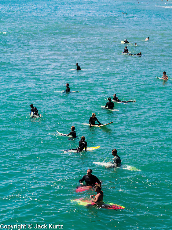 """26 JUNE 2012 - SAN CLEMENTE, CALIFORNIA: Surfers try to catch waves below the pier in San Clemente, CA. San Clemente is midway between Los Angeles and San Diego at the southern tip of Orange county. It is known for its ocean, hill, and mountain views, a pleasant climate and its Spanish Colonial style architecture. San Clemente's city slogan is """"Spanish Village by the Sea"""".  PHOTO BY JACK KURTZ"""