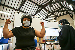 © Licensed to London News Pictures. 07/09/2021. London, UK. Antonia Dos Santos gestures after Nassima Larbi, a NHS vaccinator, administered the Pfizer Covid-19 vaccine<br /> at a vaccination centre in Tottenham, north London. Vaccines minister Nadhim Zahawi has said that Covid-19 booster jab campaign will begin later this month and dismisses media reports that the government is considering a two-week 'fire break' by extending the October half-term school holidays. Photo credit: Dinendra Haria/LNP