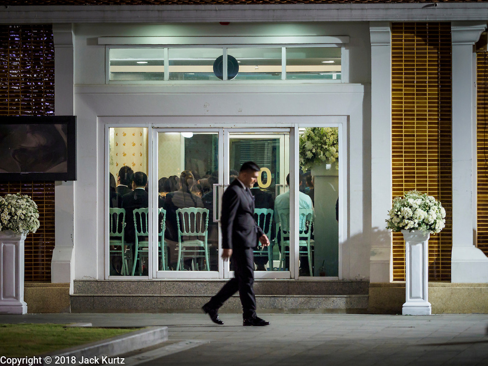 03 NOVEMBER 2018 - BANGKOK, THAILAND: A man walks past the room where the Abhidhamma Recitation Ceremony is being held on the first day of funeral rites for Vichai Srivaddhanaprabha at Wat Debsirin in Bangkok. Vichai was the owner of King Power, a Thai duty free conglomerate, and the Leicester City Club, a British Premier League football (soccer) team. He died in a helicopter crash in the parking lot of the King Power stadium in Leicester after a match on October 27. Vichai was Thailand's 5th richest man. The funeral is expected to last one week.   PHOTO BY JACK KURTZ